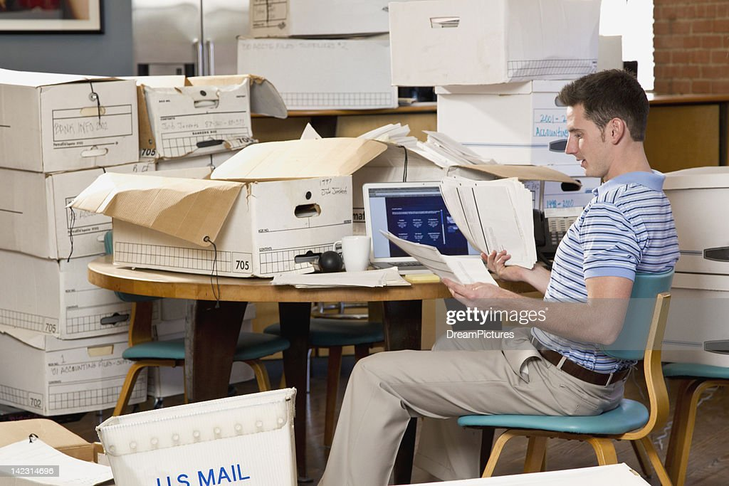 Man in an office over flowing with paperwork : Stock Photo