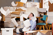 Man in an office over flowing with paperwork