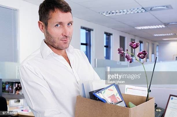 man in an office with personal belongings in a box