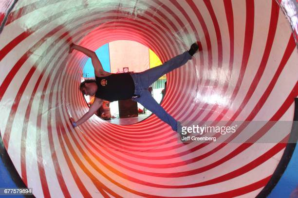 A man in an optical illusion rotating tube at the New Mexico State Fair