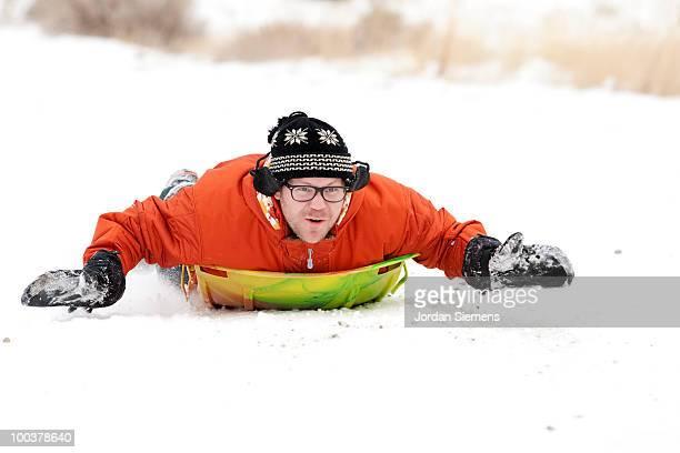 Man in an orange jacket sledding.