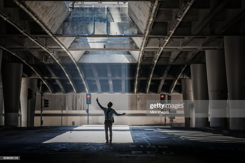 A man in an urban underpass, with concrete and glass structures surrounding them, taking a selfie.