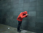 Man in anorak struggling against wind, pulling hood over head