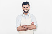 Confident young handsome man in apron keeping arms crossed and smiling while standing against white background