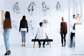 Man sitting on stool and looking at drawings while spending time in art center with other visitors