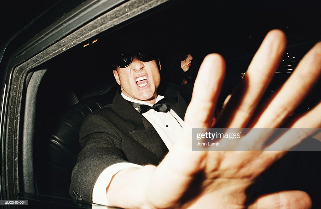 Man in back of limousine raising hand to camera, close-up : Stock Photo