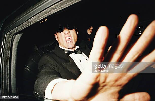 Man in back of limousine raising hand to camera, close-up