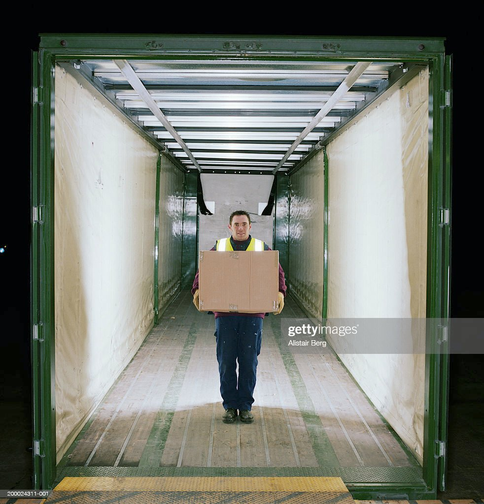 Man in back of lorry holding cardboard box, portrait : Stock Photo