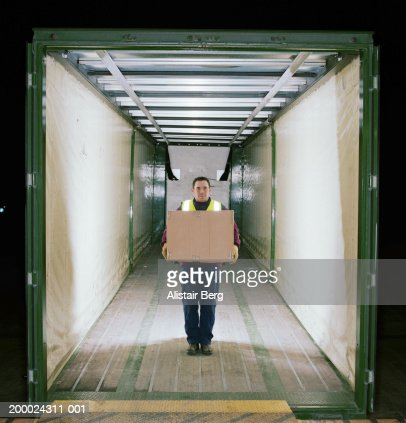 Man in back of lorry holding cardboard box, portrait