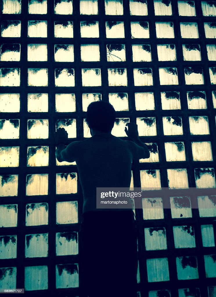 A man in backlight on the window of an old factory : Foto de stock