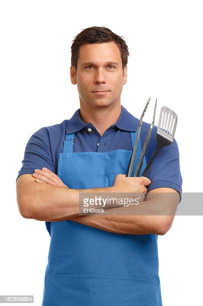 Man in barbecue apron with cooking utensils on white