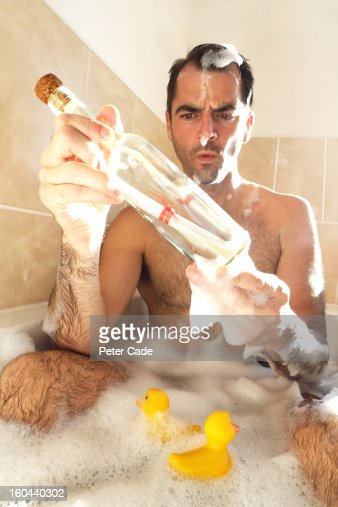 Man in bath with ducks holding message in a bottle : Stock Photo
