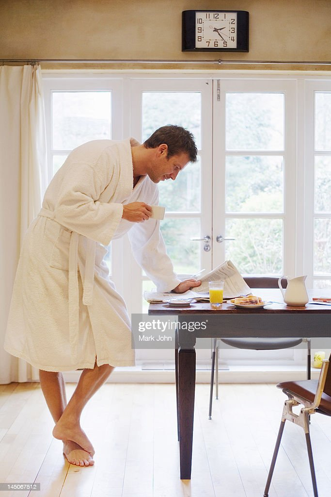 Man in bathrobe having breakfast