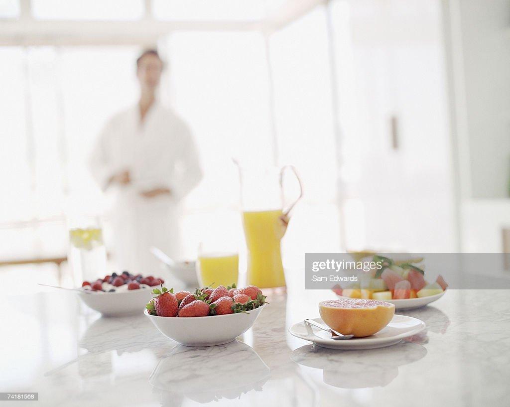 Man in bathrobe with fruit berries and orange juice : Stock Photo