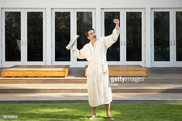 Man in Bathrobe Yawning, Stretching and Getting Morning Newspaper