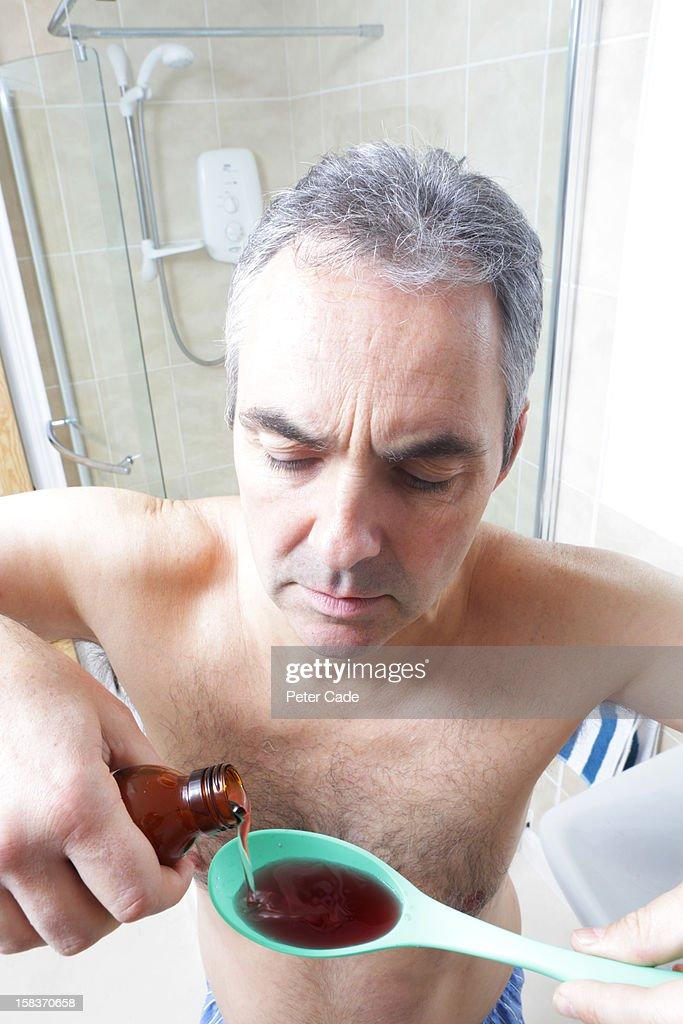 Man in bathroom pouring medicine into spoon : Stock Photo