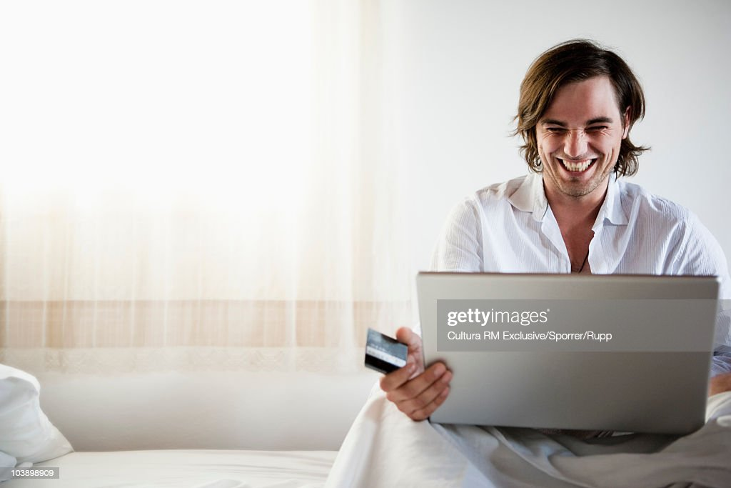 Man in bed shopping online : Stock Photo