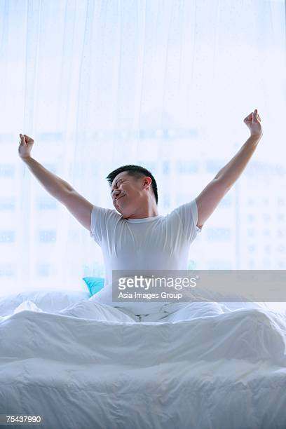 Man in bed, stretching