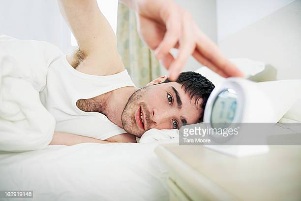 man in bed turning off alarm clock i
