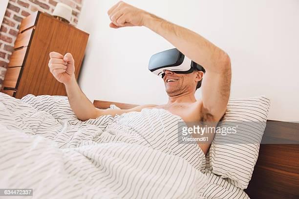 Man in bed wearing virtual reality glasses steering