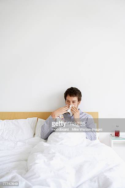 Man in Bed with a Cold Blowing His Nose
