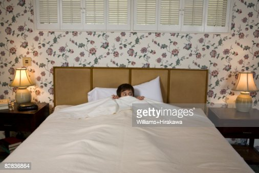 Man in bed with scared look : Stock Photo