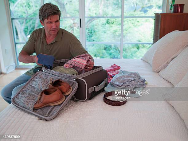 Man in bedroom packing suitcase