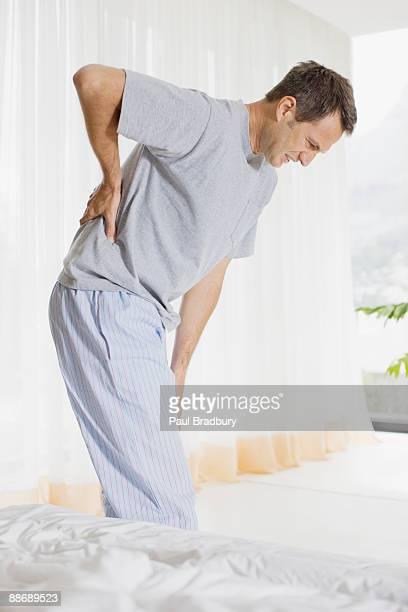 Man in bedroom with backache