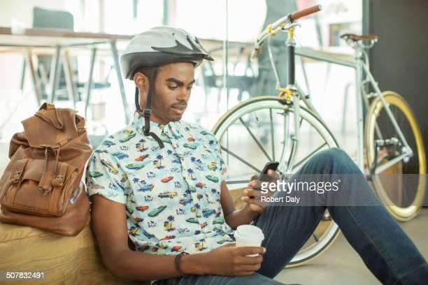 Man in bicycle helmet using cell phone in office