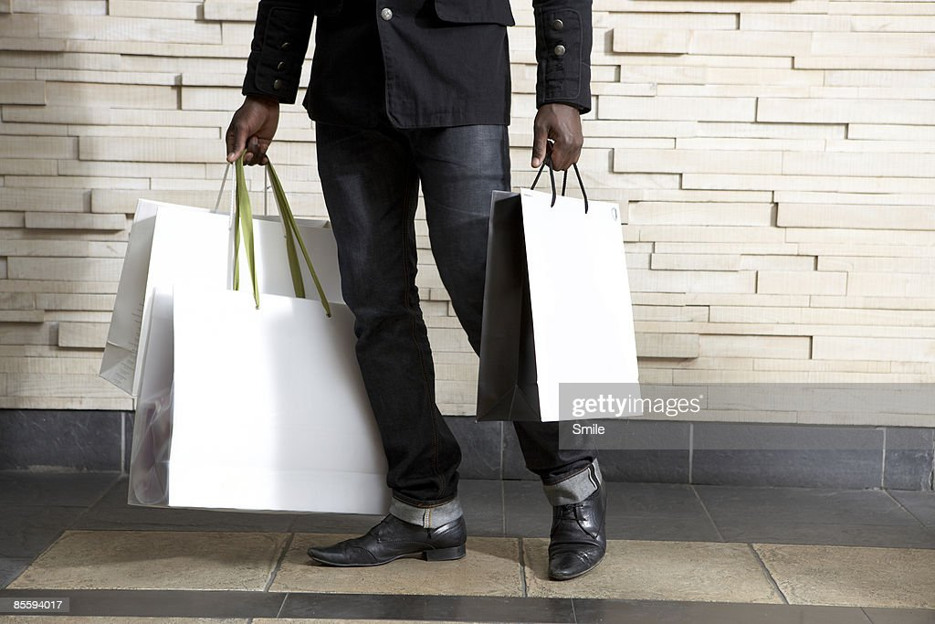 man in black carrying bags, legs only : Stock Photo