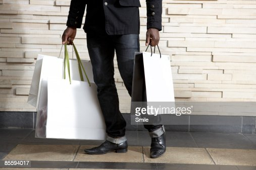 man in black carrying bags, legs only : Foto de stock