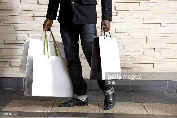 man in black carrying bags, legs only