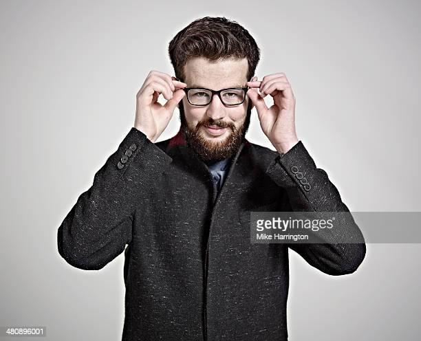 Man in black coat holding edges of his glasses.