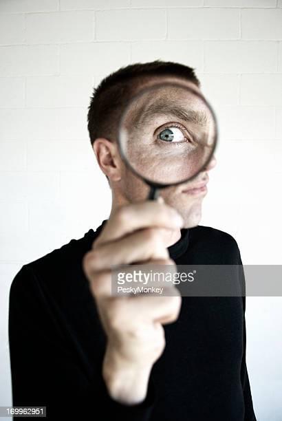 Mann in Schwarz hat einige Spion Überwachung mit Lupe