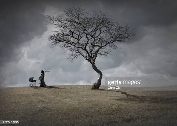 Man in black robes with baby carriage by dead tree