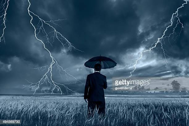Mann in schwarzer Anzug mit einem schwarzen Regenschirm in einem Sturm