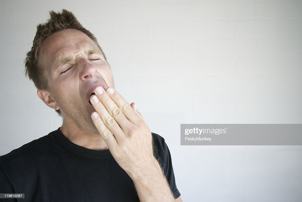 Man in Black T-Shirt Yawns