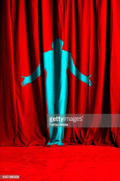 Man in blue against a red curtain shrugging his shoulders