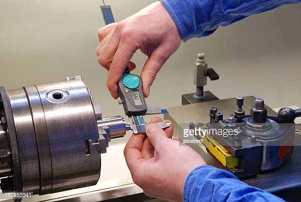Man in blue shirt measuring parts with a digital caliper