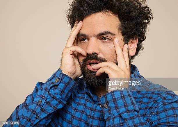 Man in blue shirt posing seductively with hands