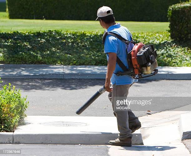 Man in blue shirt using a leaf blower on a sidewalk