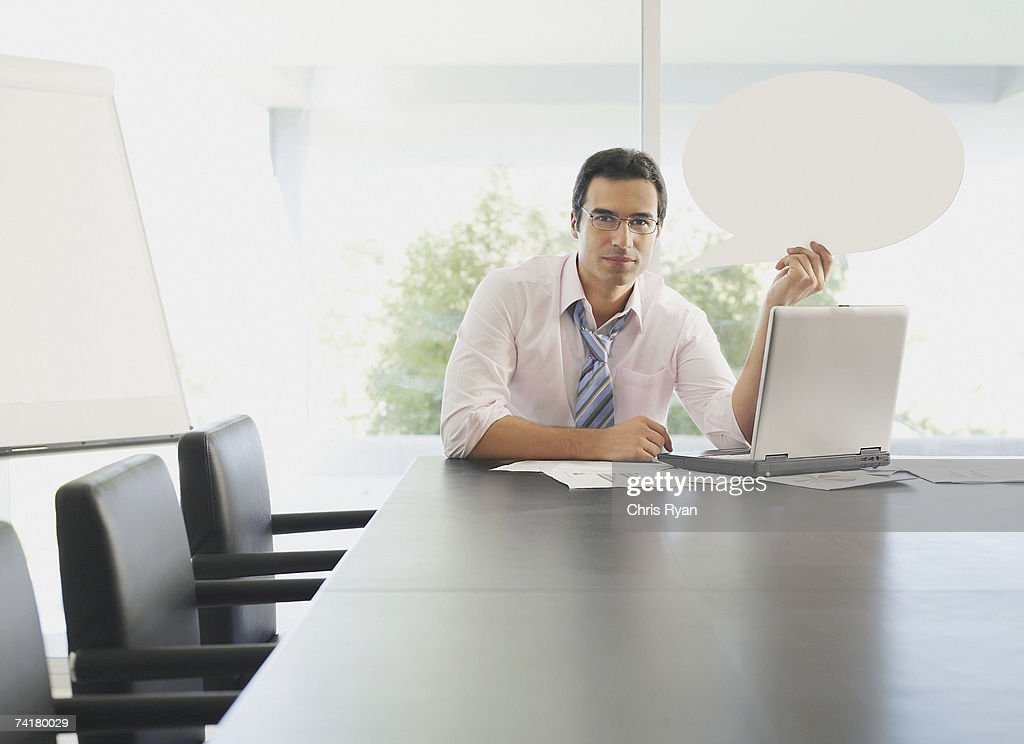 Man in boardroom with word balloon and laptop : Stock Photo