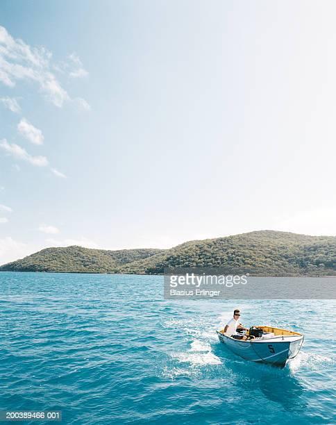 Man in boat, island in background