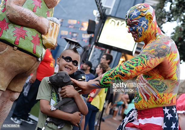 A man in body paint pets a puppy held by sevenyearold Ashton Ritz on the first day of the 45th annual ComicCon in San Diego California July 24 2014...