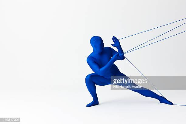 Man in bodysuit playing with string