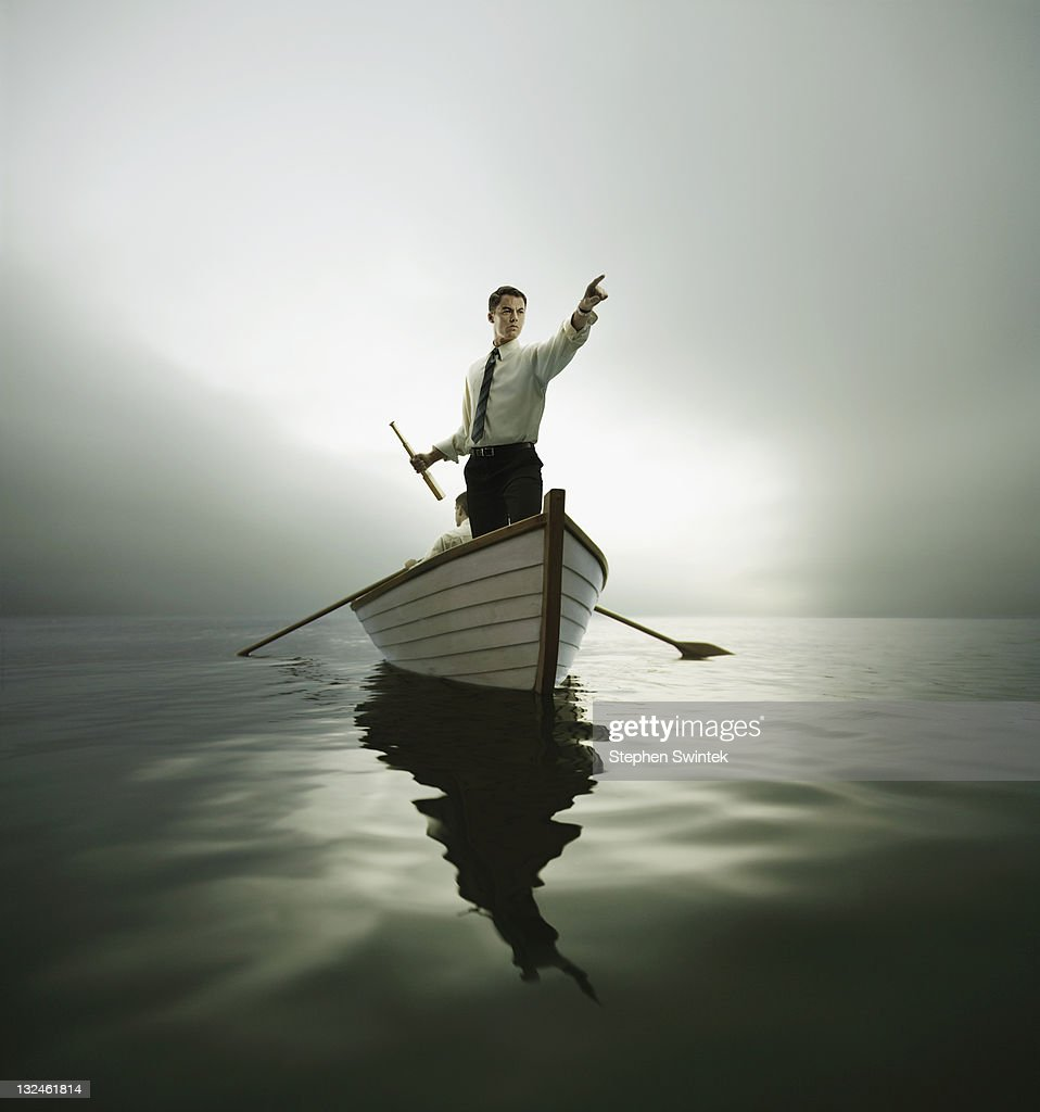 Man in bow of boat pointing : Stock Photo