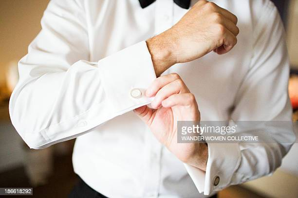 Man in bow tie doing up cuff ring on white shirt