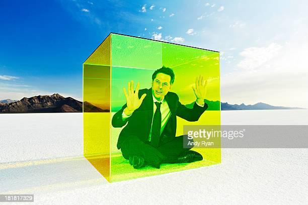 Man in box on salt flats, hands on glass.