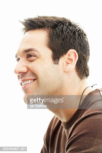 Man in brown shirt smiling, profile