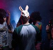 Man in bunny mask dancing in night club